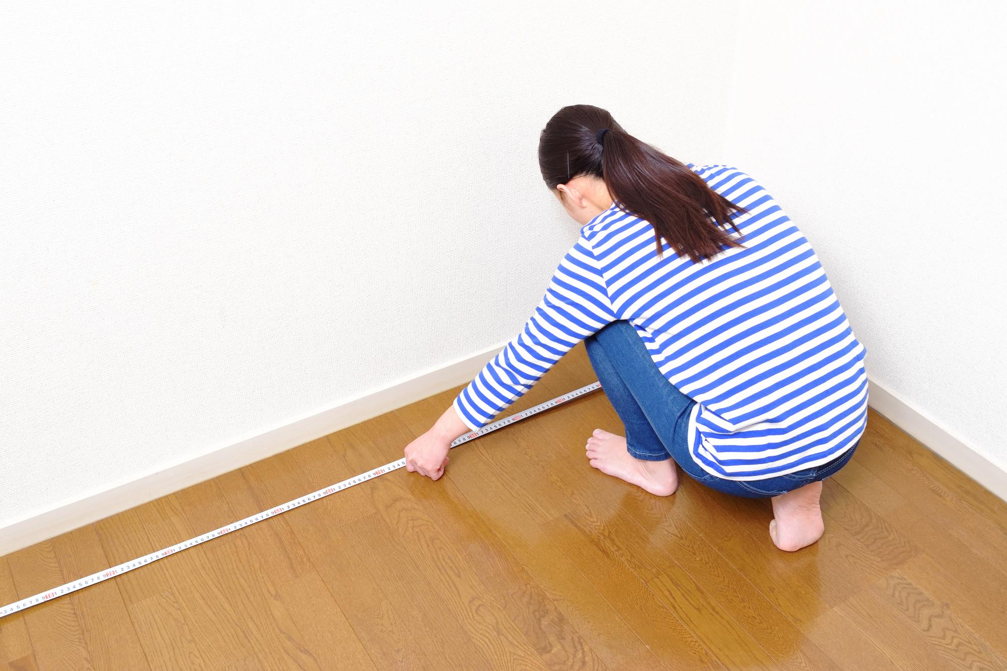 部屋のサイズを測る女性