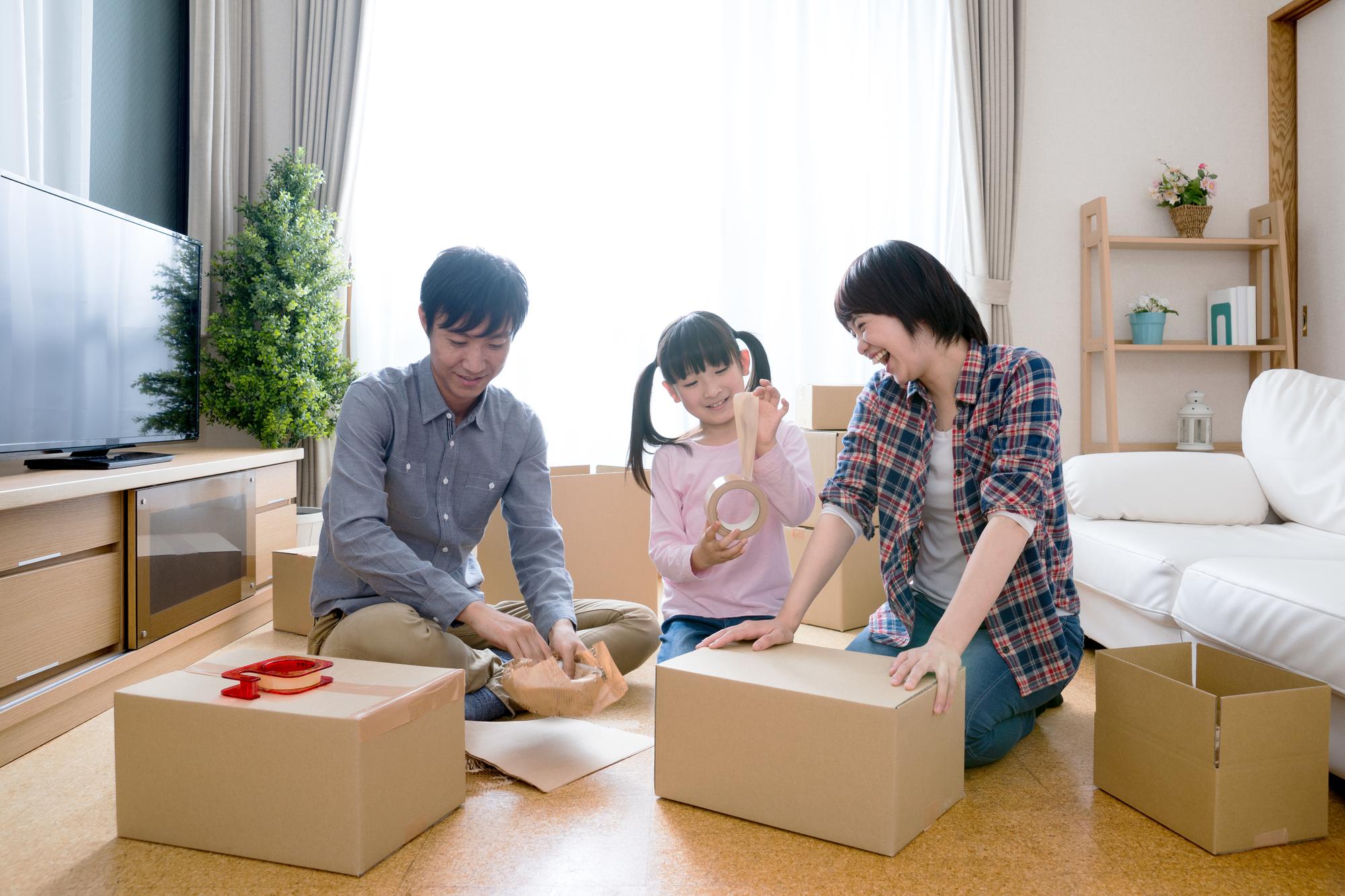ダンボールに引越し荷物を梱包する家族