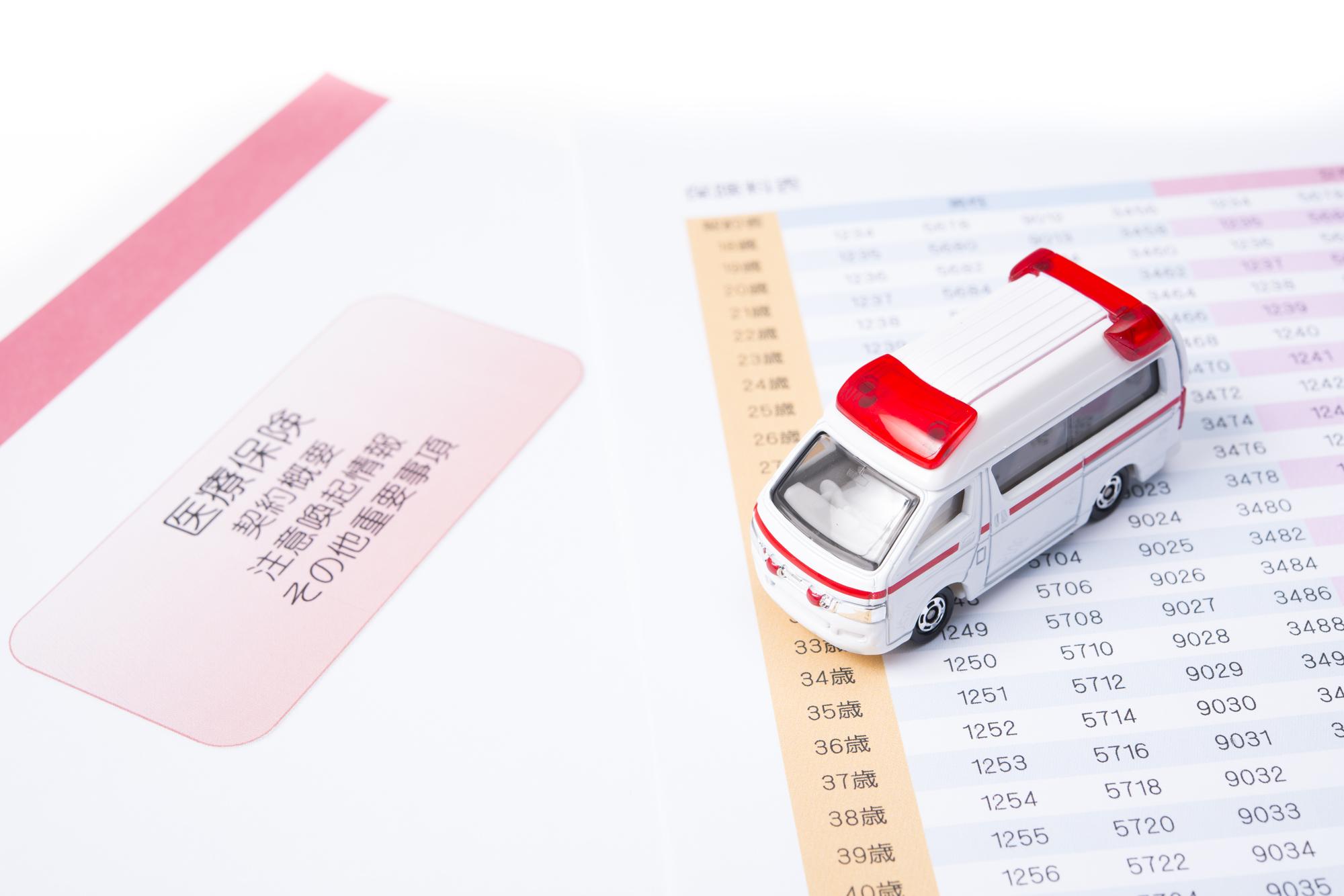 医療保険についての冊子と救急車のおもちゃのミニカー