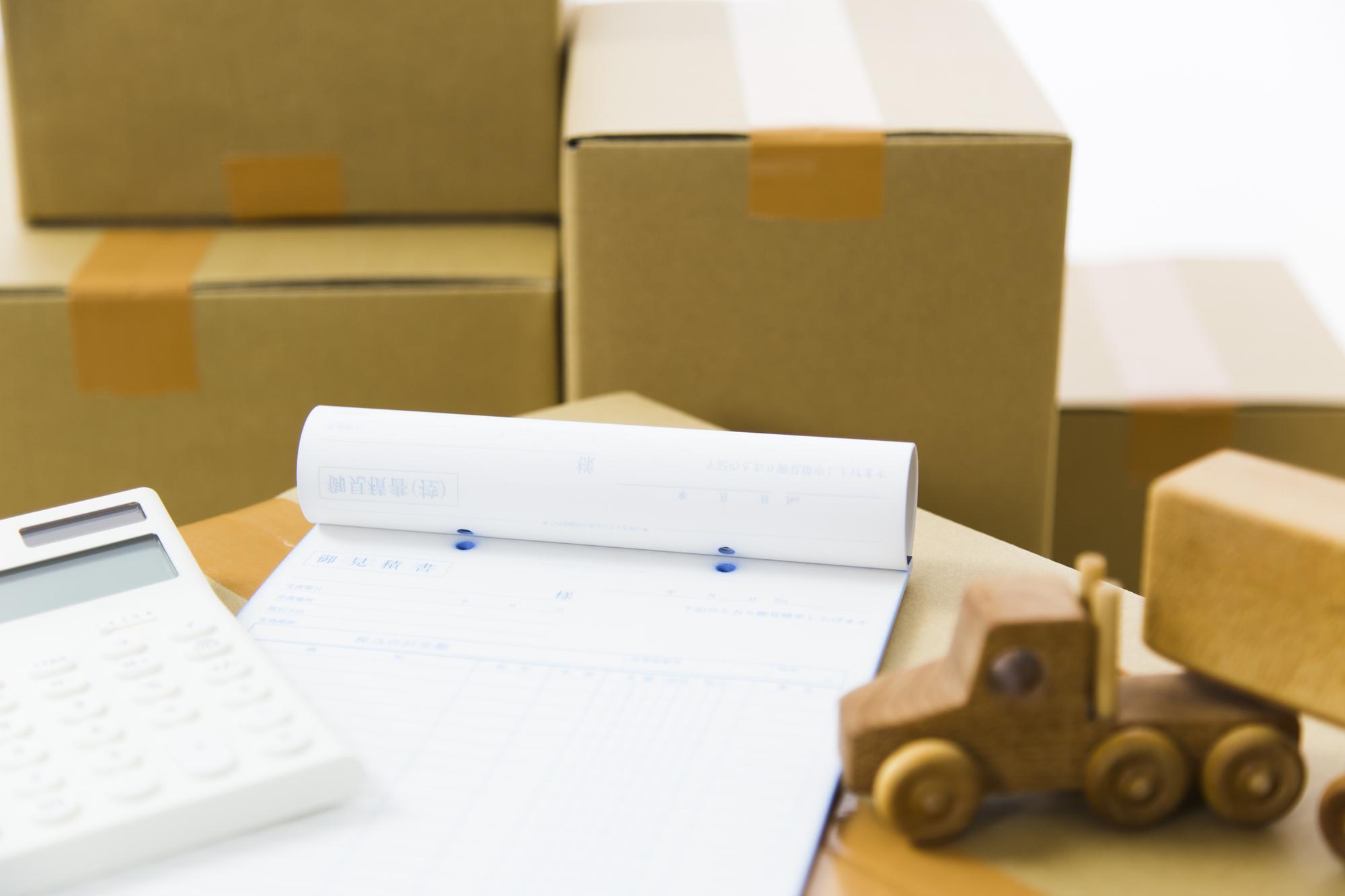 引越しの見積もり書と電卓とおもちゃのトラックと荷物の段ボール