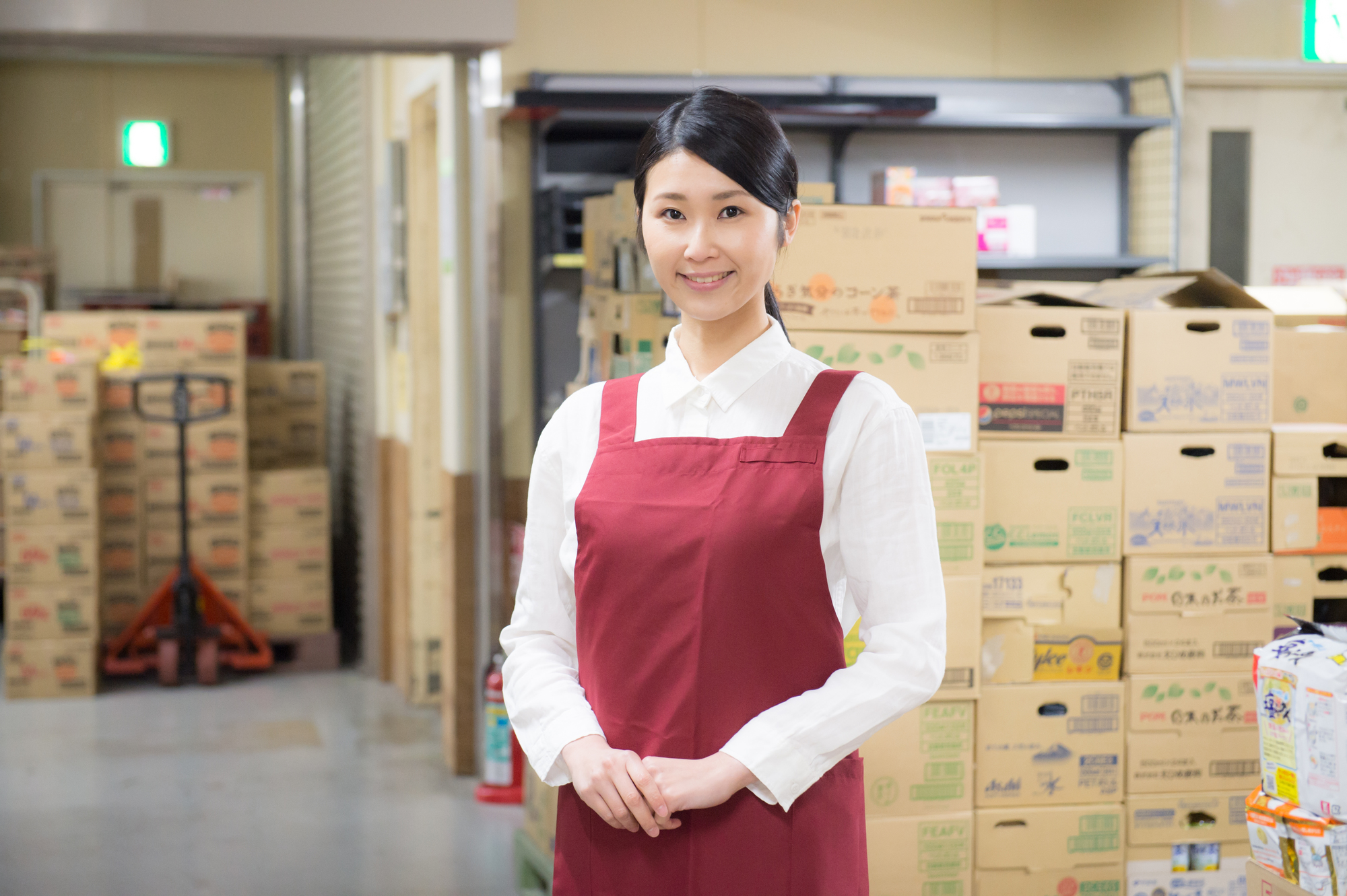スーパーマーケットでダンボールに入った商品の前で微笑む店員の女性