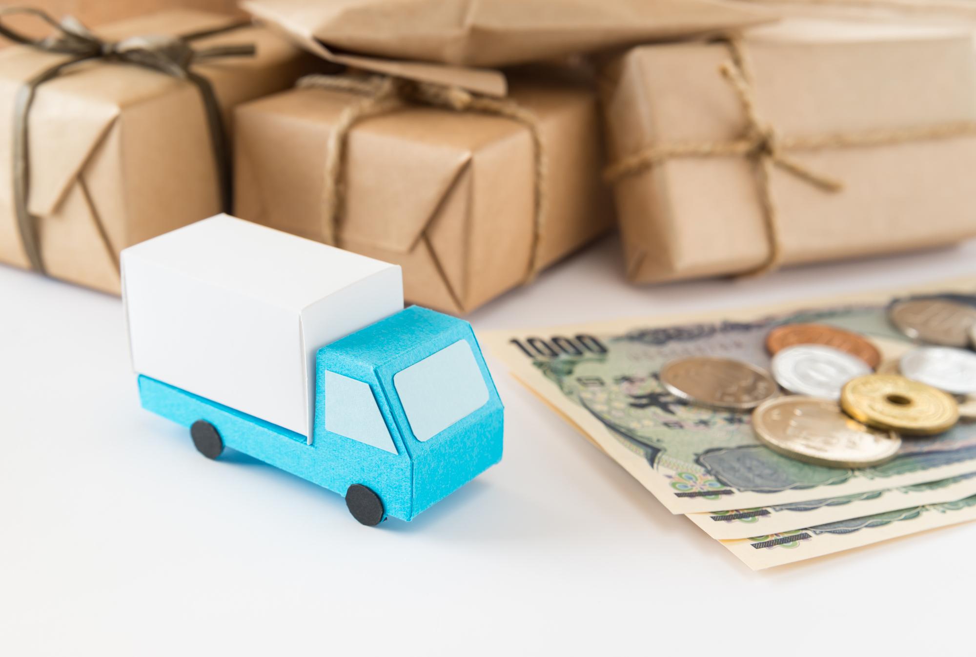 紙製の引越しトラックと荷物のミニチュア模型とお金