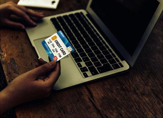 クレジットカードを持ちながらパソコンで作業する人