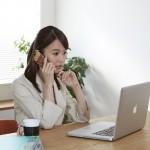 引越し前にインターネット解約・更新の電話をする女性