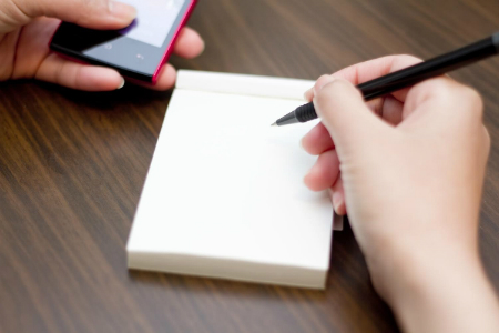 引越しに必要な手続きについて調べるスマートフォンとメモ帳とペン