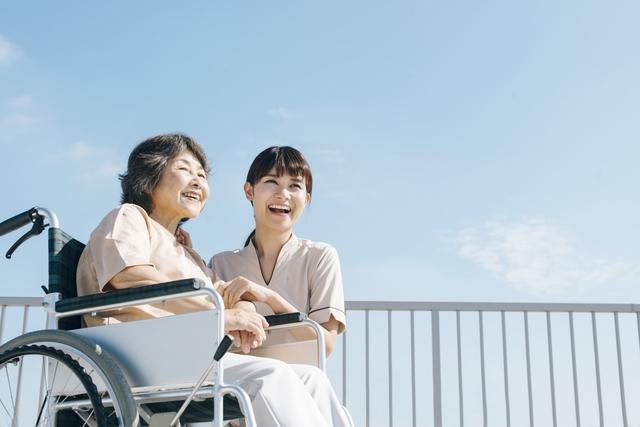 車椅子の高齢女性と介護スタッフ