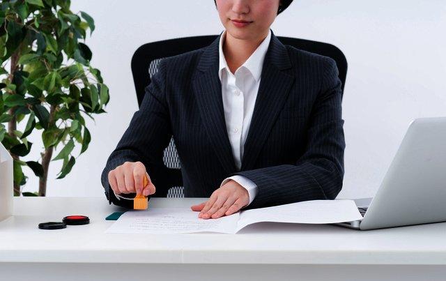 書類に押印しようとしているスーツ姿の女性