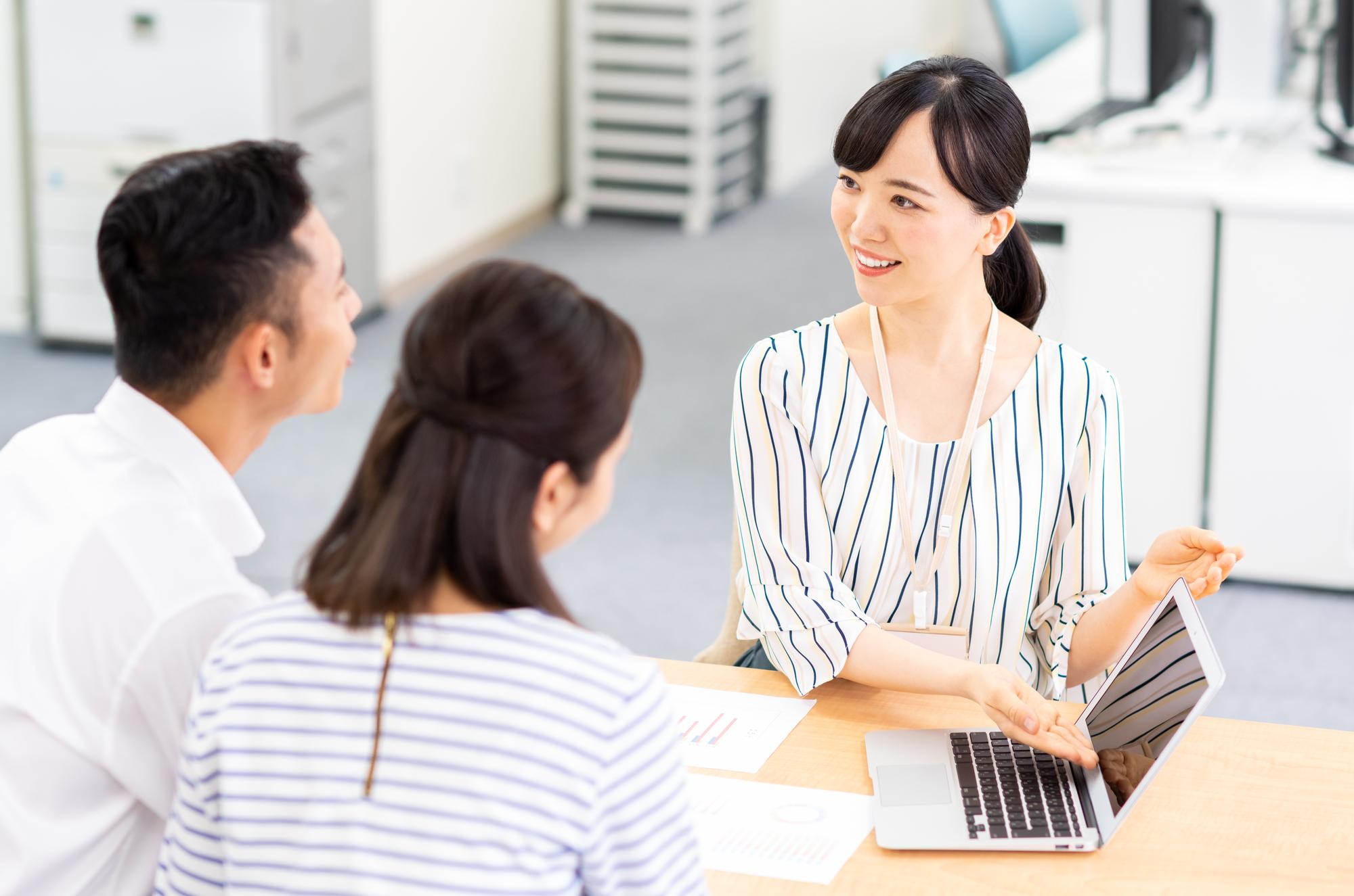 若い夫婦がビジネスウーマンに相談するイメージ写真