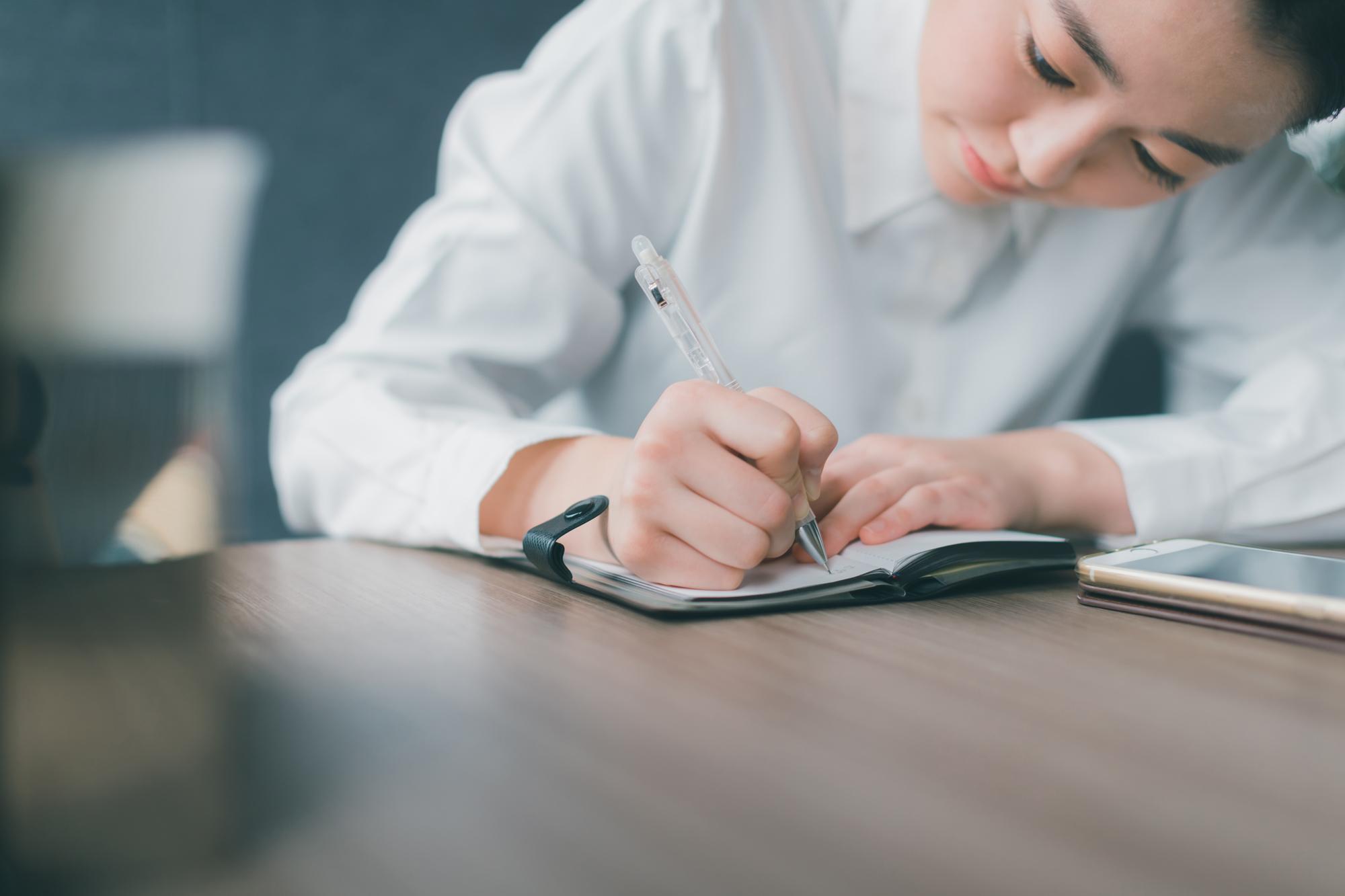 引っ越し前に必要なことを書き出す女性