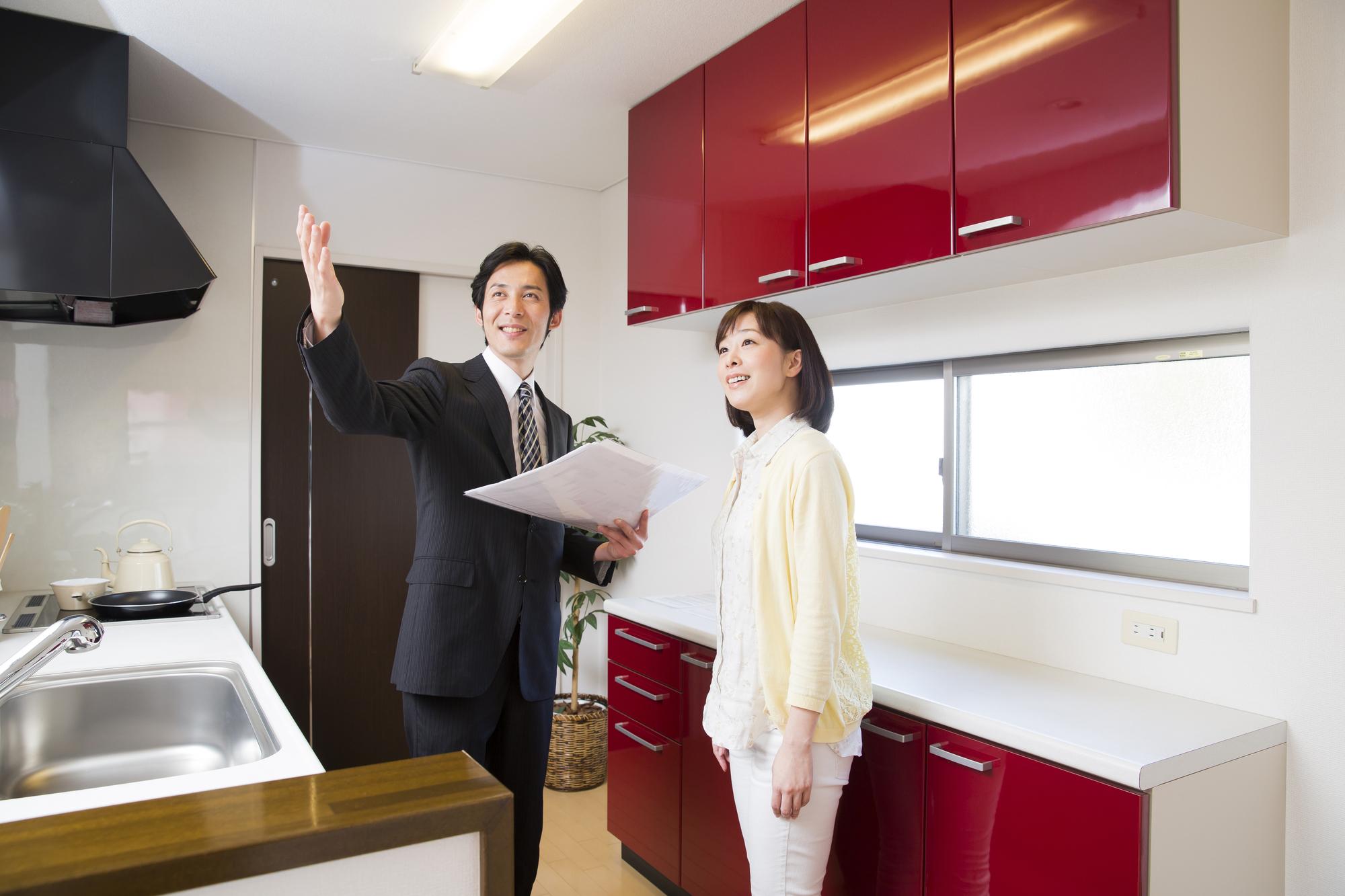 キッチンでビジネスマンに説明をうける女性