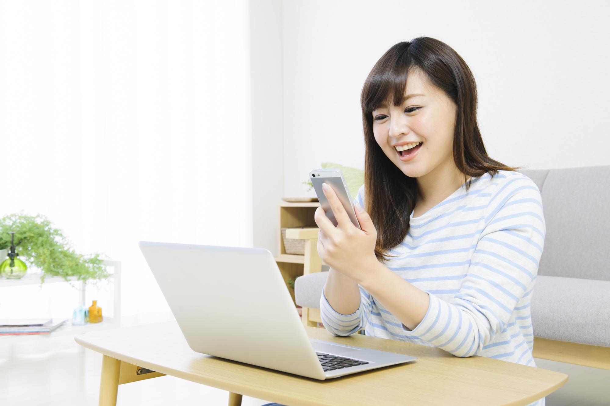 パソコンとスマホをする若い女性