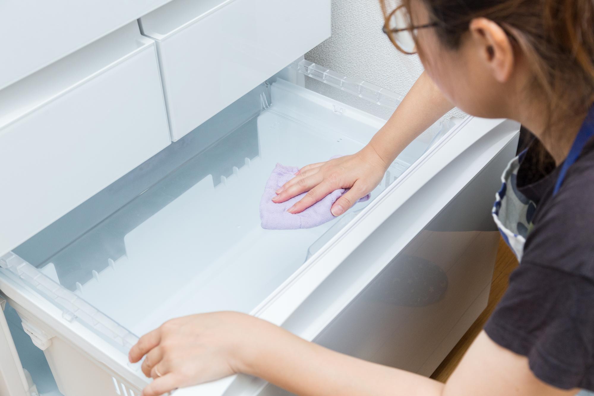冷蔵庫の拭き掃除をする女性
