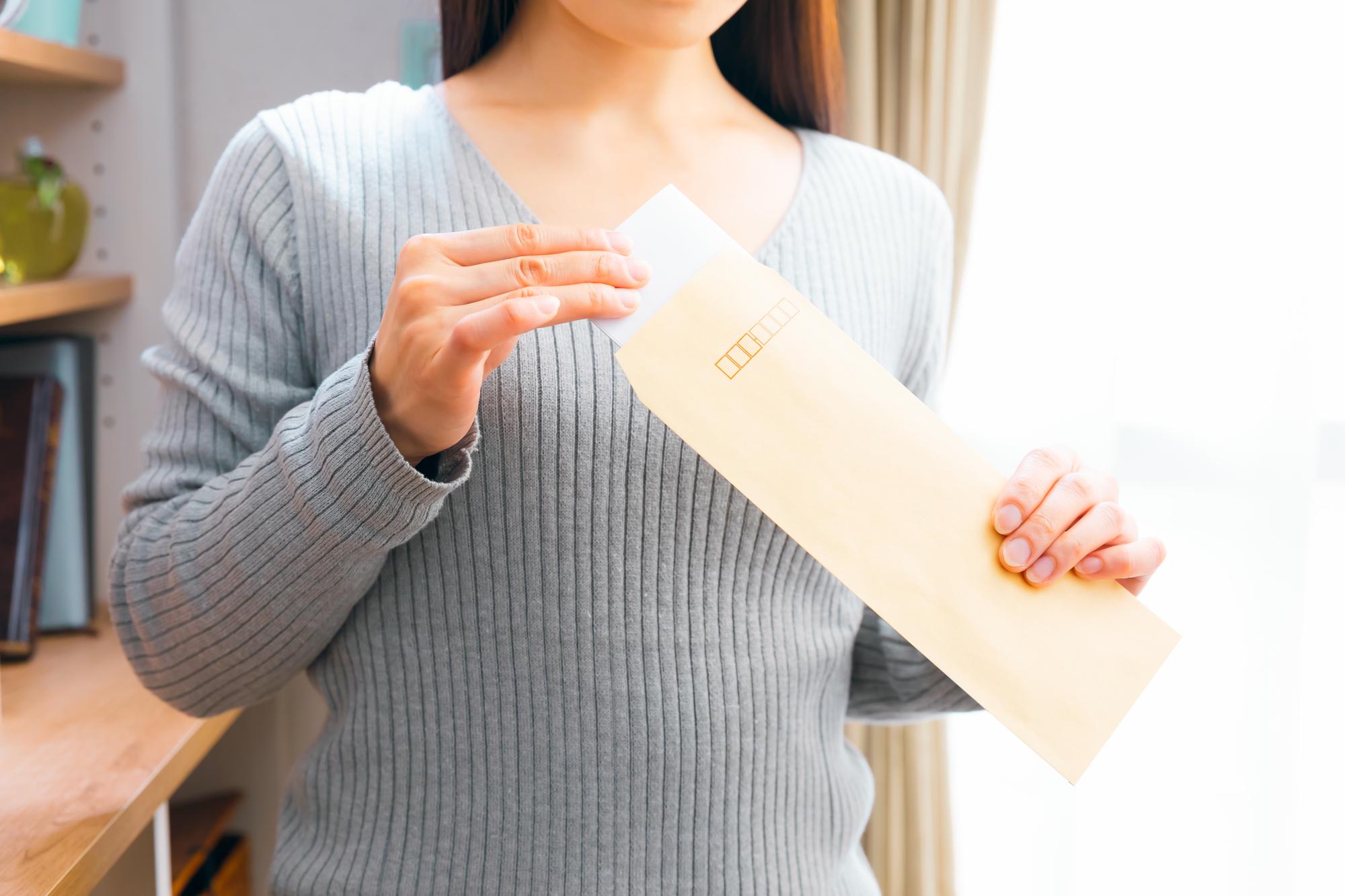 封筒を持つ女性