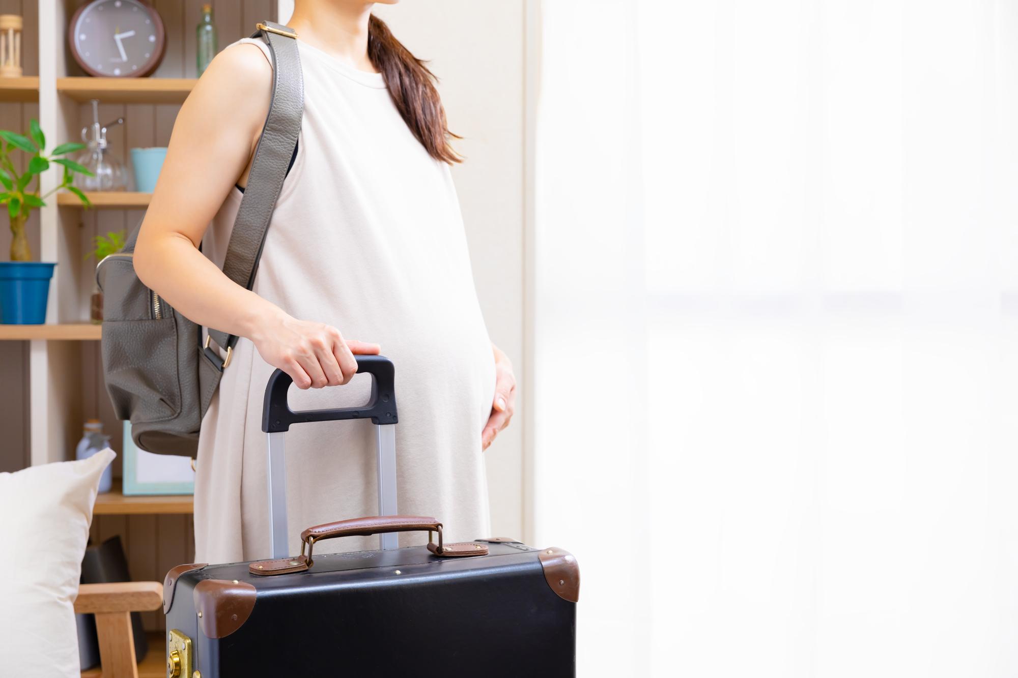 旅行鞄を持つ妊婦