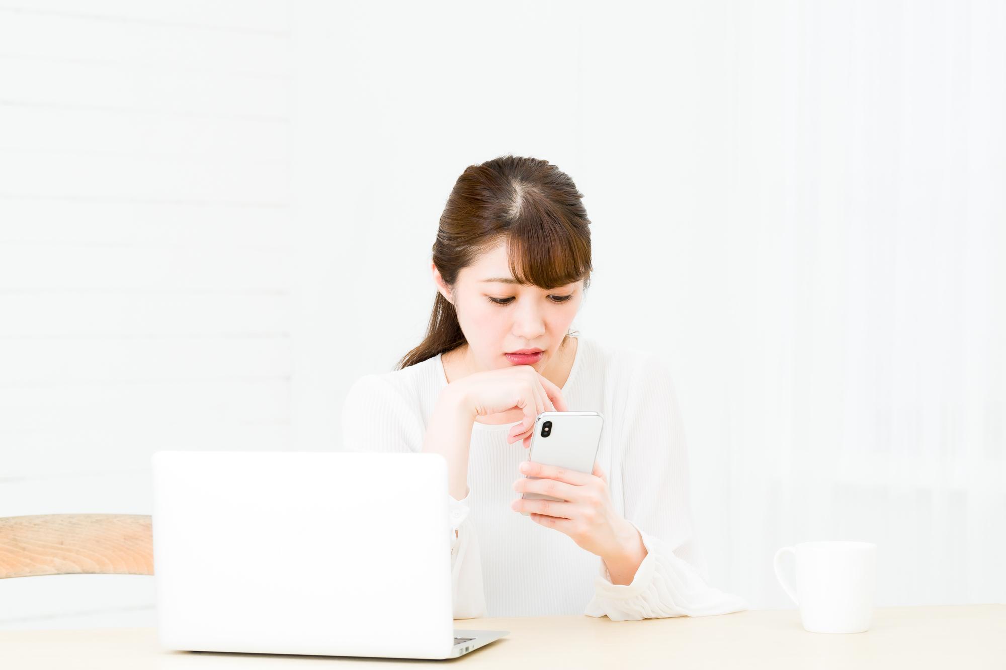 パソコンとスマホを使う若い女性