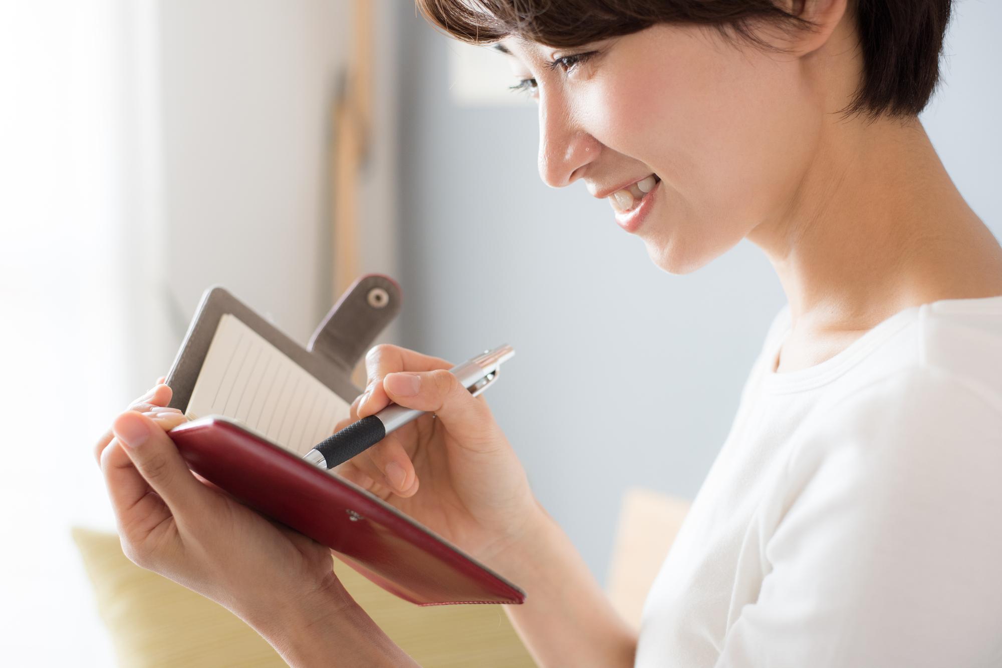 手帳にメモを取る女性