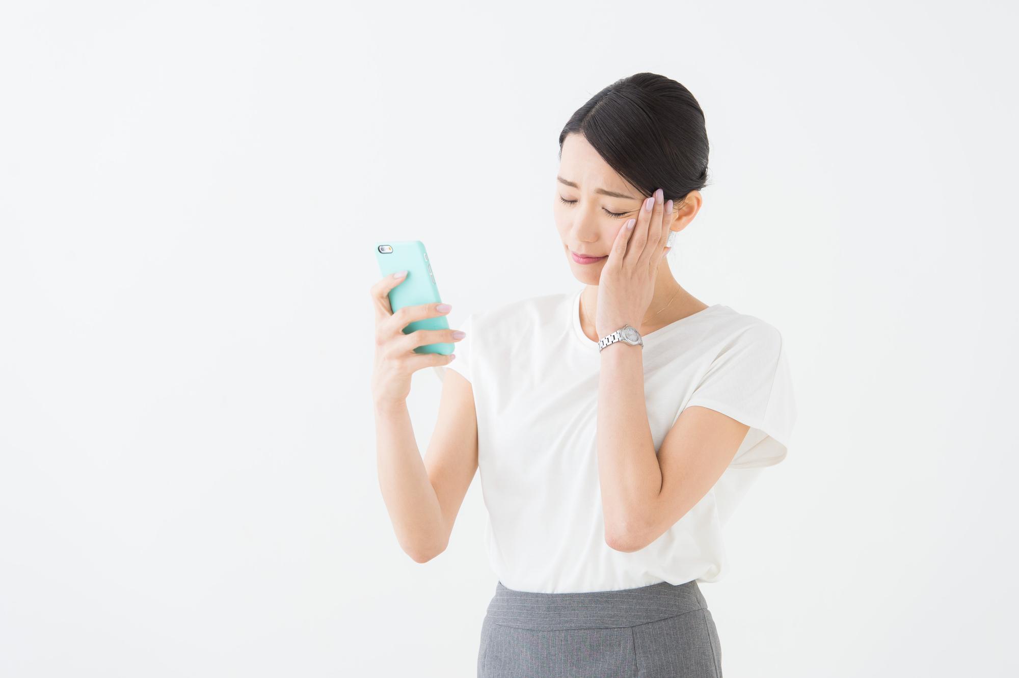 スマートフォンを持って考える女性