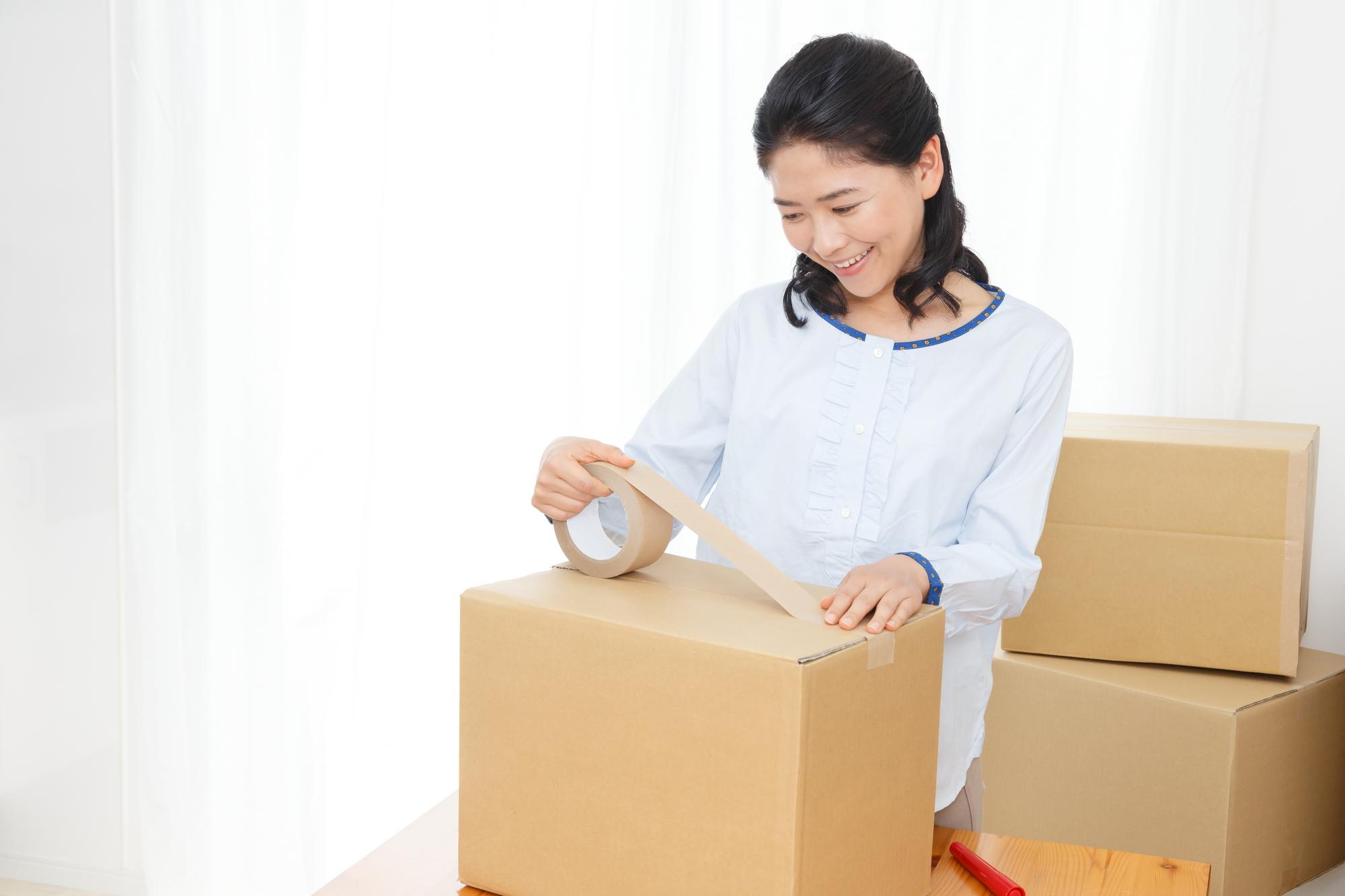 ダンボールを梱包する女性