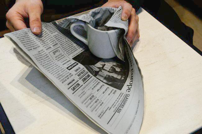 取っ手のあるカップを新聞紙で包む